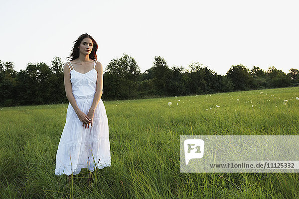 Woman standing in meadow with hands clasped