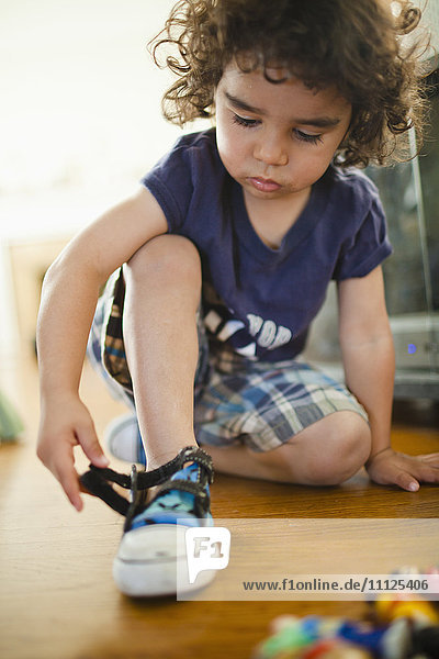 Mixed race boy fastening shoes