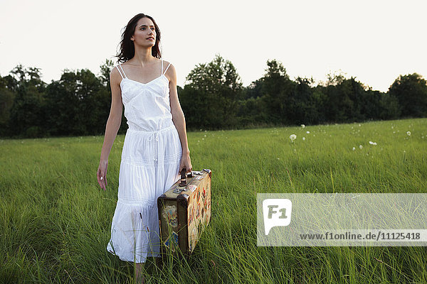 Woman walking with suitcase through meadow