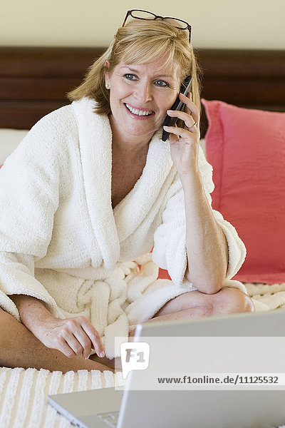 Caucasian woman talking on cell phone on bed