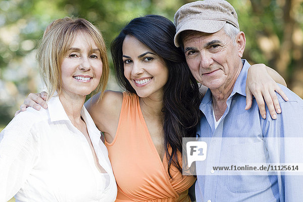 Hispanic family smiling outdoors