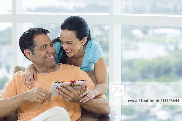 Hispanic couple hugging in armchair