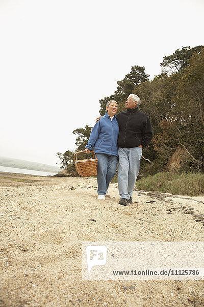 Senior Asian couple walking on beach with picnic basket