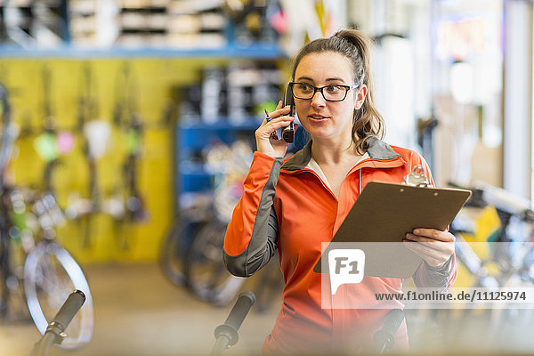 Caucasian woman talking on telephone in bicycle shop