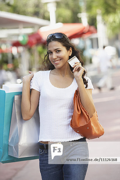 Hispanic woman holding shopping bags