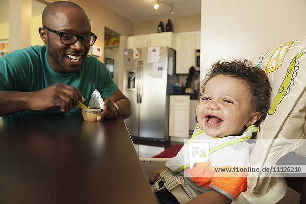 Father feeding baby at table