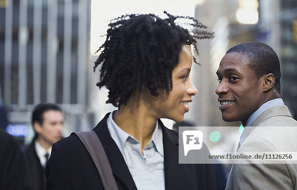 African American businesswoman smiling at businessman on street