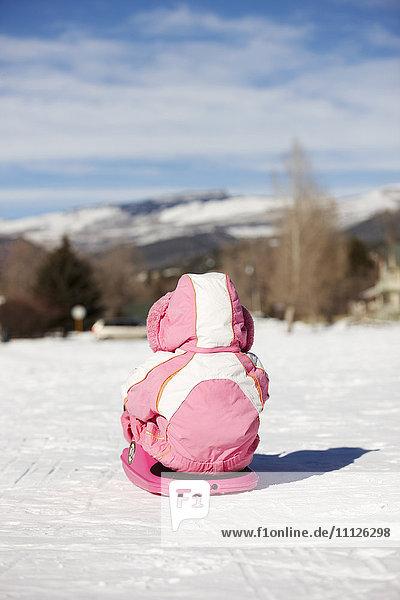 Mixed race girl sledding in snow