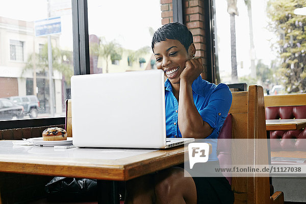 African American businesswoman using laptop in restaurant