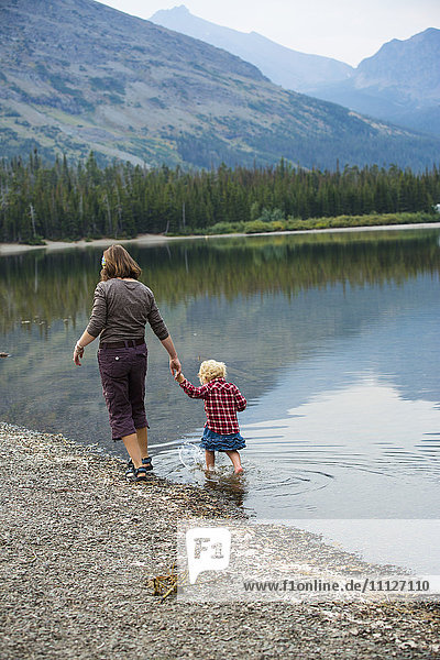 Mother and child walking in still rural lake