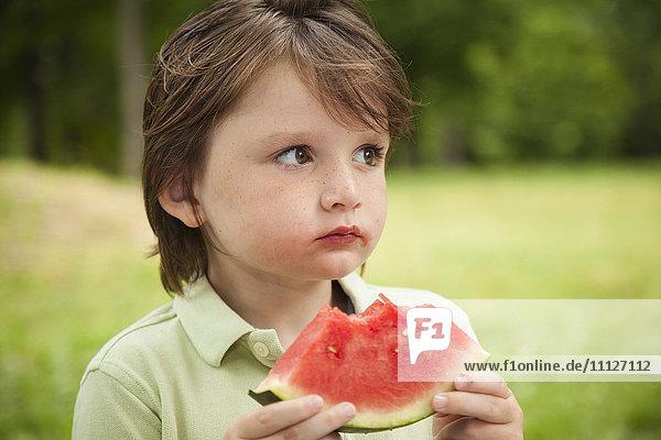 Caucasian boy eating watermelon outdoors
