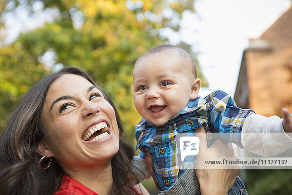 Smiling mother holding baby outdoors