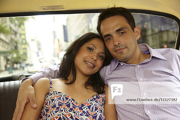 Couple hugging in back of taxi