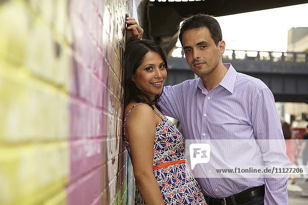 Couple leaning on urban wall