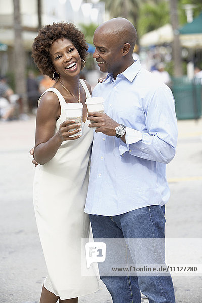 African American couple drinking take out coffee