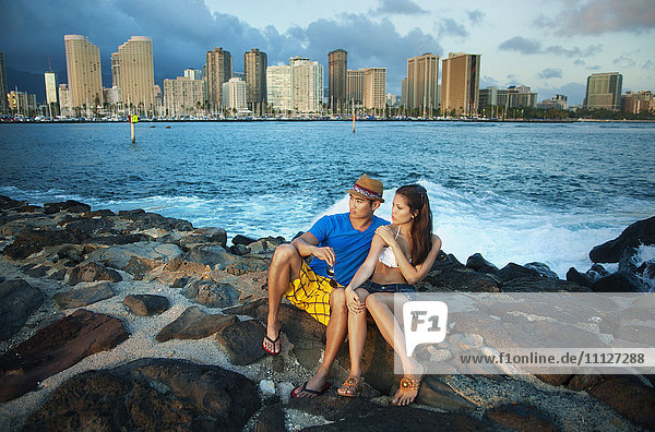 Couple sitting together on rocky shore