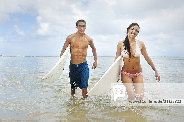 Couple walking in ocean carrying surfboards