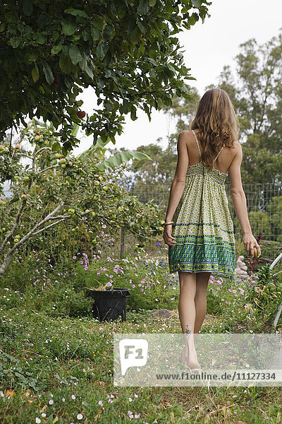 Mixed race woman talking next to fruit trees
