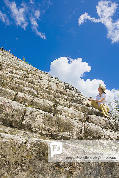 Asian woman sitting on Mayan temple steps