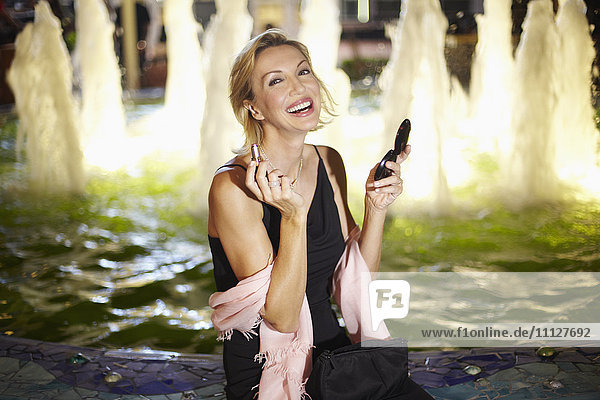 Caucasian woman putting on make up near fountain