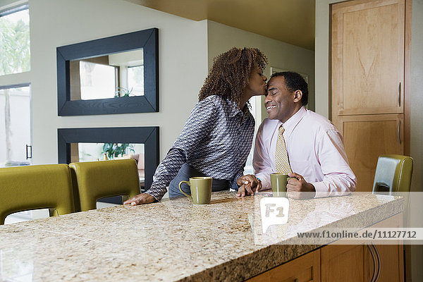 African woman kissing husband in modern kitchen