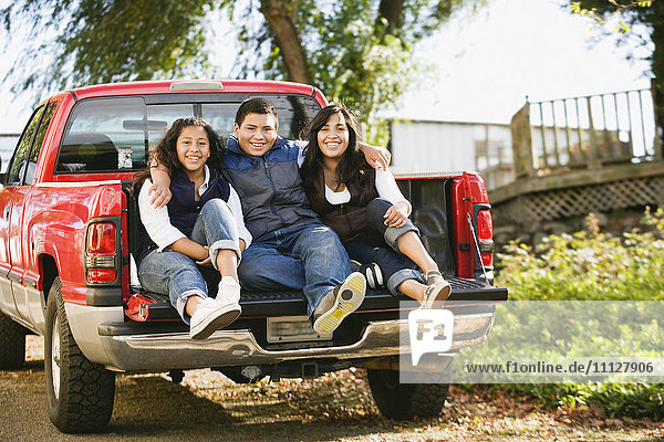 Hispanic siblings sitting in bed of truck