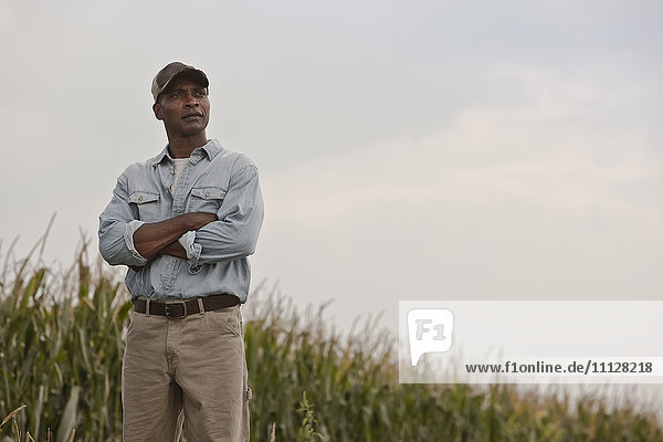 African American man standing in field with arms crossed