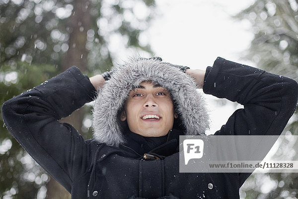 Mixed race man in hooded coat outdoors in snowfall