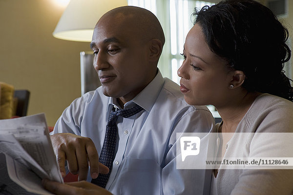 African couple reading newspaper