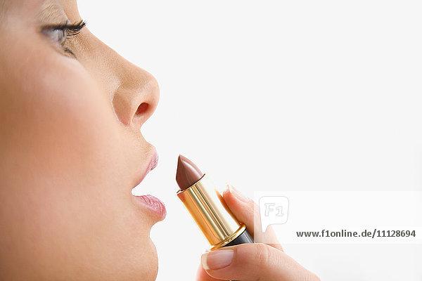 Mixed race woman applying lipstick