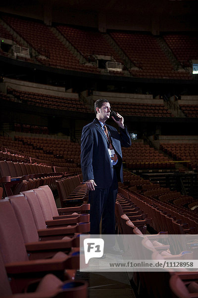 Businessman using walkie-talkie in empty auditorium