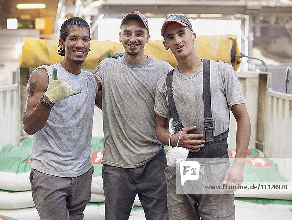 Hispanic workers hugging in factory