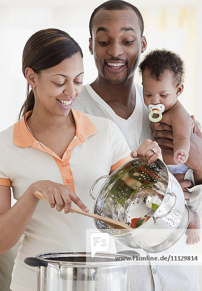African couple and baby cooking