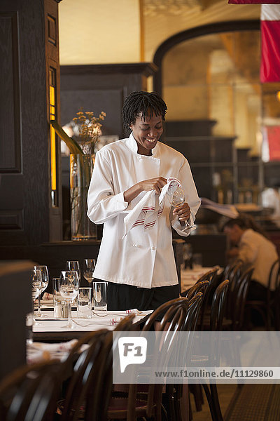African American waitress checking wine glass in restaurant