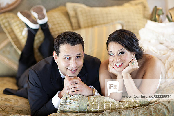Egyptian bride and groom laying on bed