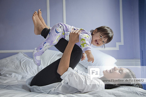 Sri Lankan mother playing with baby girl on bed