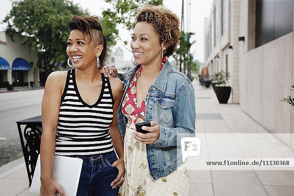 Friends standing together in city sidewalk