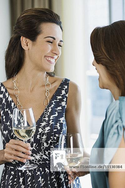 Hispanic women drinking white wine