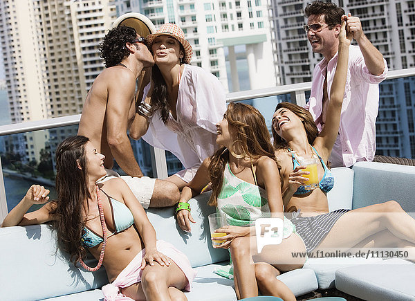 Hispanic men and women partying on rooftop