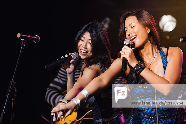 Asian women singing and pointing onstage