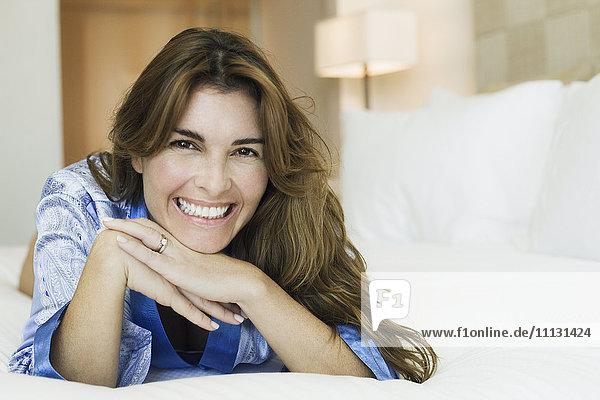 Smiling Hispanic woman laying on bed