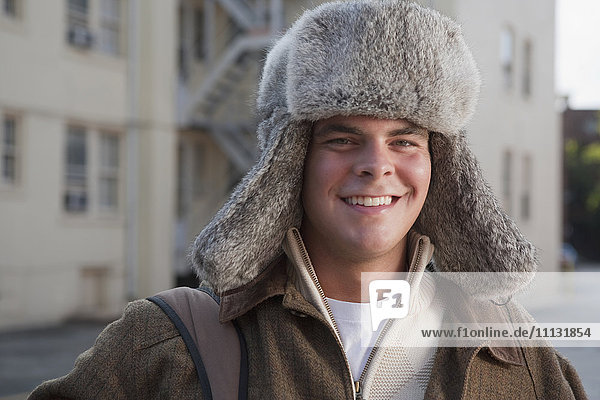 Mixed race man wearing fur hat