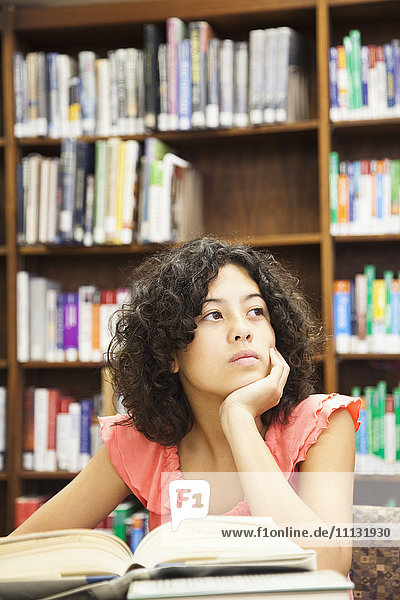 Mixed race girl doing homework in library