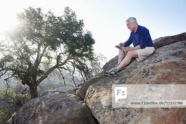 Caucasian man using digital tablet in remote area