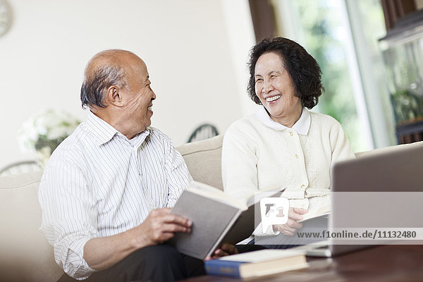 Chinese couple with book and laptop