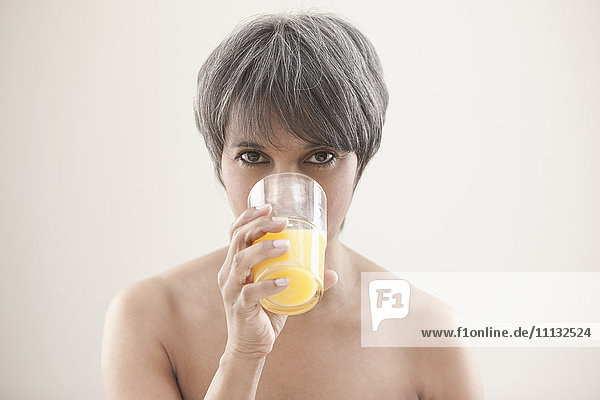 Mixed race woman drinking orange juice