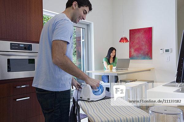 Husband ironing while wife uses laptop