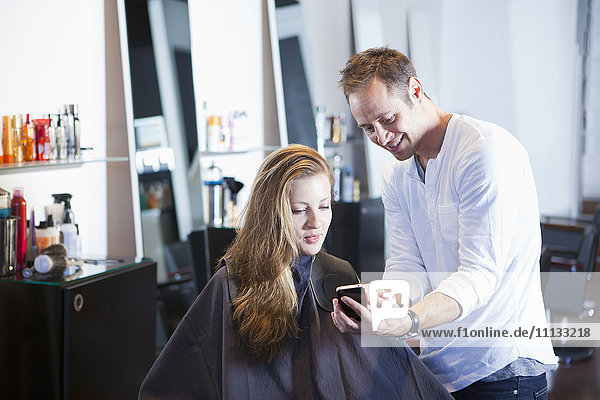 Hairdresser showing cell phone to client