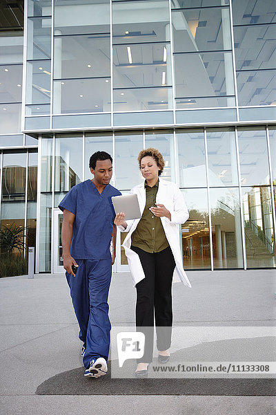 Doctor and co-worker looking at digital tablet