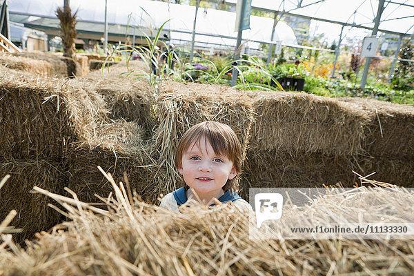 Caucasian boy standing near hay bales